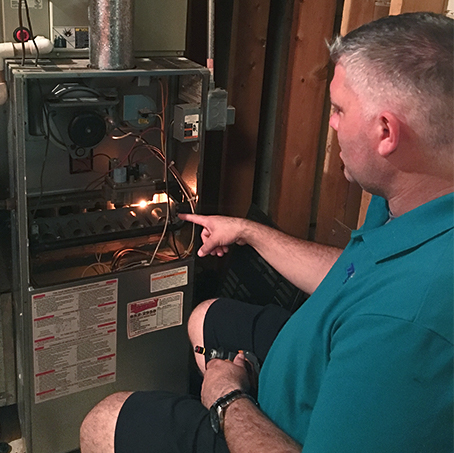 Service technician cleaning a furnace