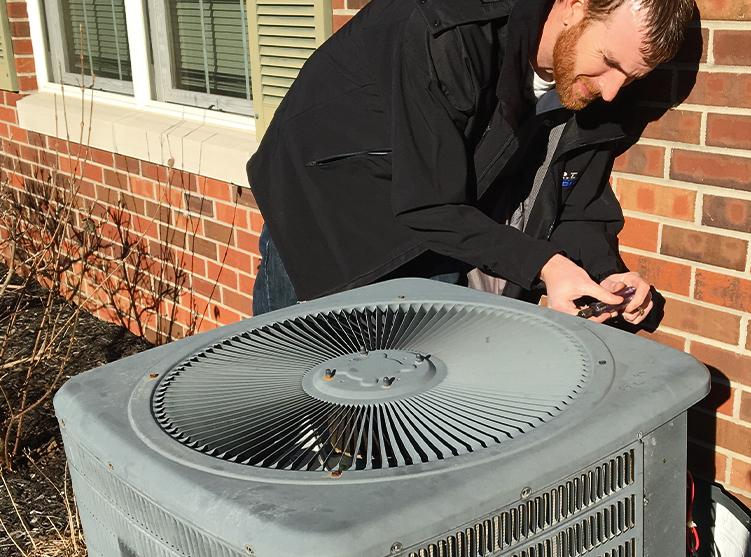 RT Moore Service Technician Repairing an HVAC