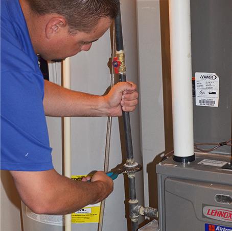 Service technician repairing a water heater gas line